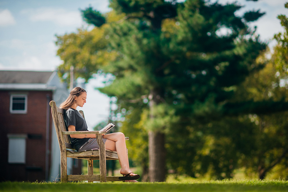 UVF Student sitting on bench and reading