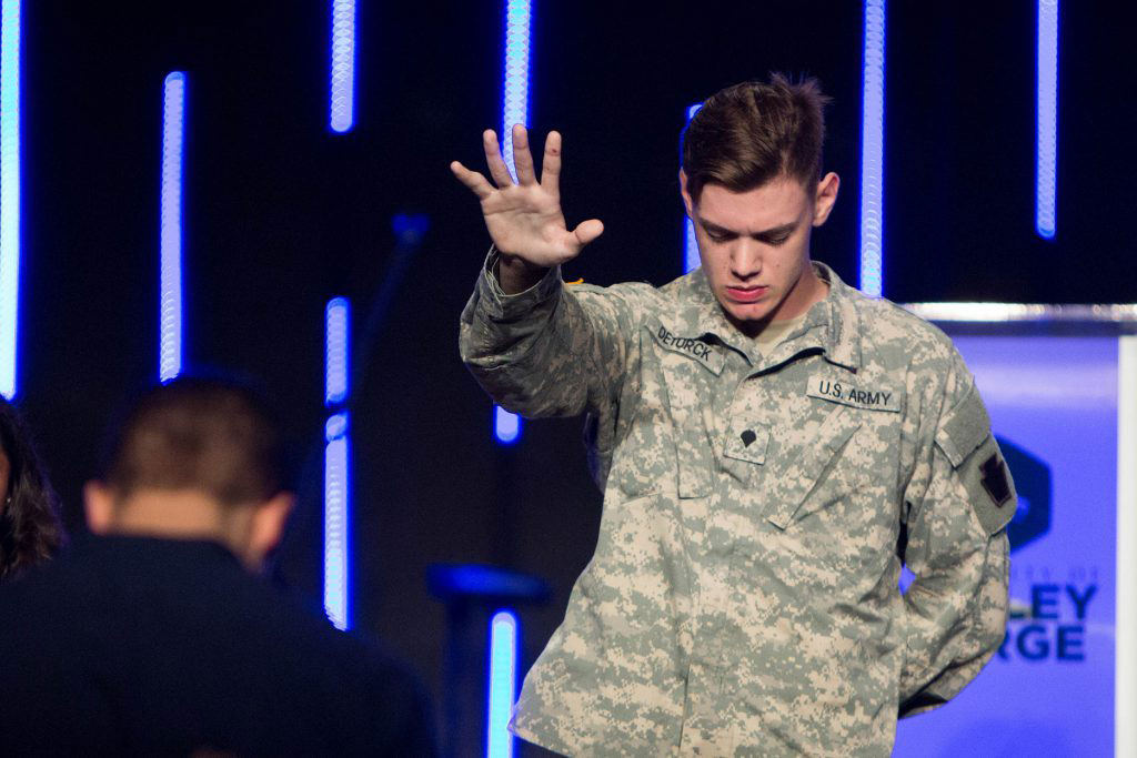 Military Student praying over student congregation