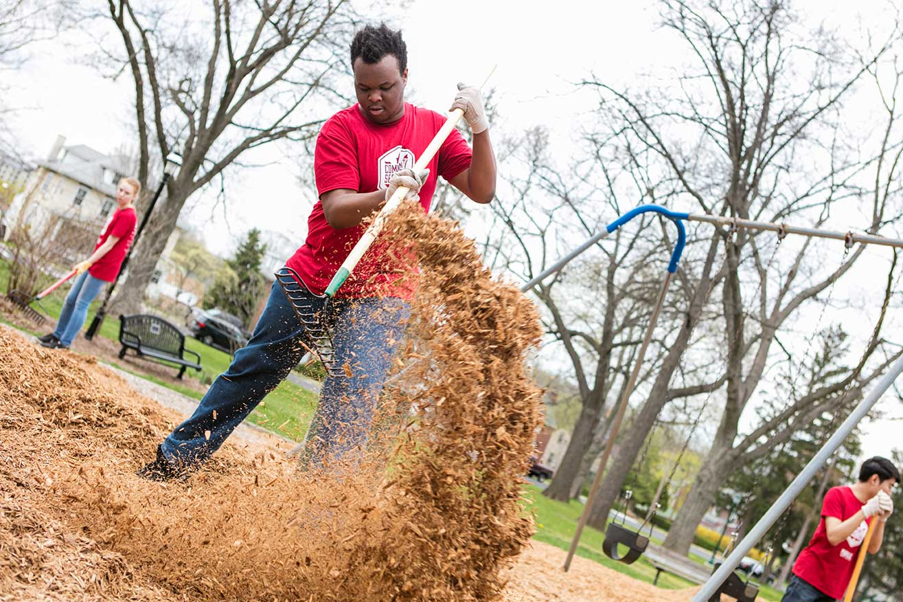 UVF Student shoveling mulch during Community Service Day