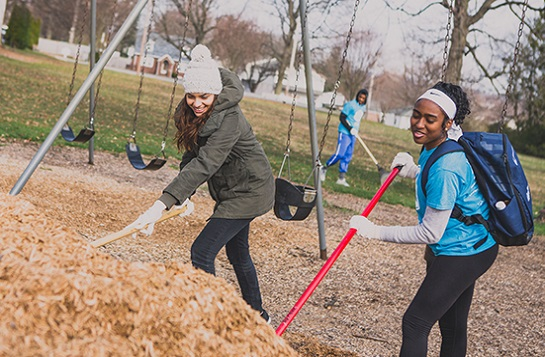 2 students mulching a playground
