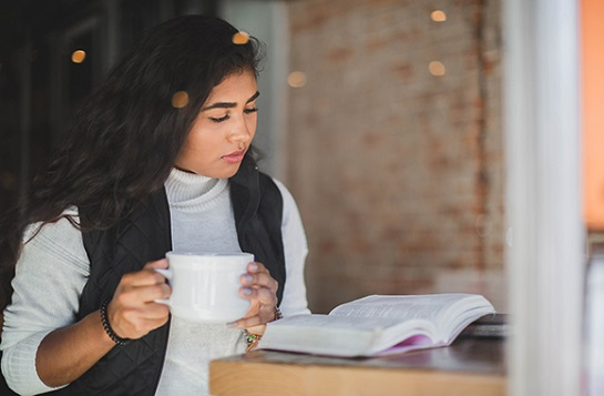 Student drinking coffee while reading the Bible