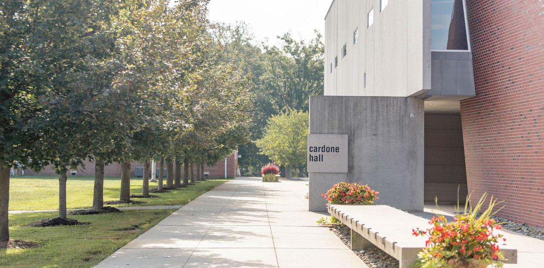 Picture of tree line, sidewalk, and part of Cardone hall