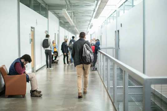 Student walking through hallways of Capeci Hall