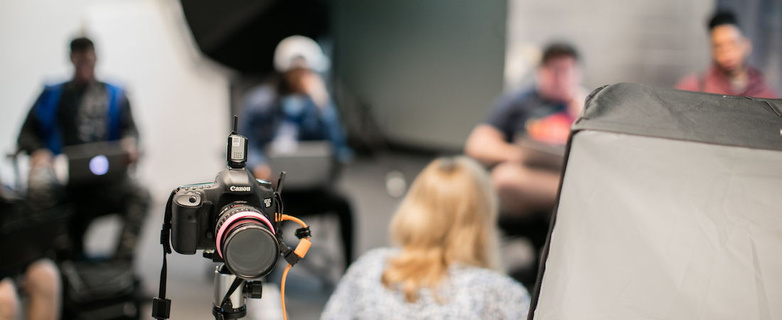 A camera in the foreground with a photography class going on behind